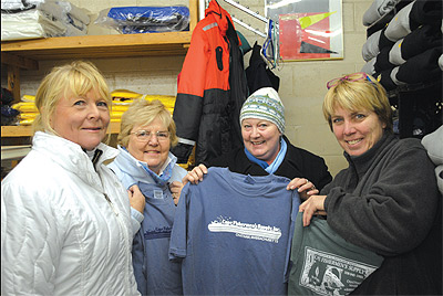 "Shoppers descended on Cape Fishermen's Supply last Wednesday in Chatham's first ""cash mob"" event, scooping up items such as the store's iconic T-shirts, held up by (from right) Brenda Saul Thompson, Sally Campbell, Linda Lucas and Sue Linnell. AMY TAGLIAFERRI PHOTO"